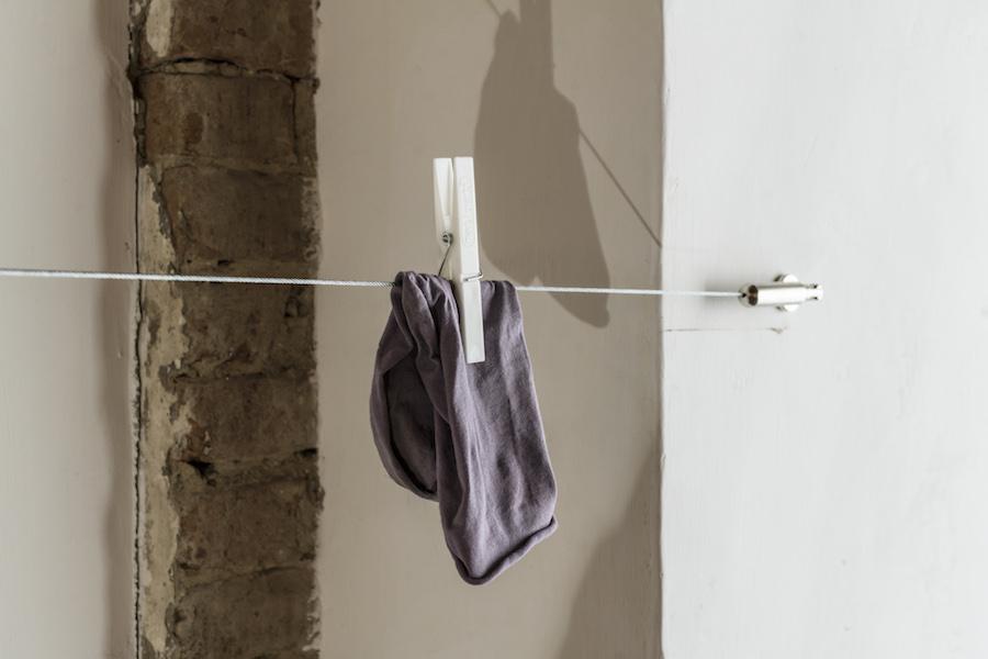 Rosa Aiello, Filo da bucato (re), 2017, (particolare). Filo di acciaio, materiali in acciaio, mollette da bucato, calzini Foto OKNOstudio